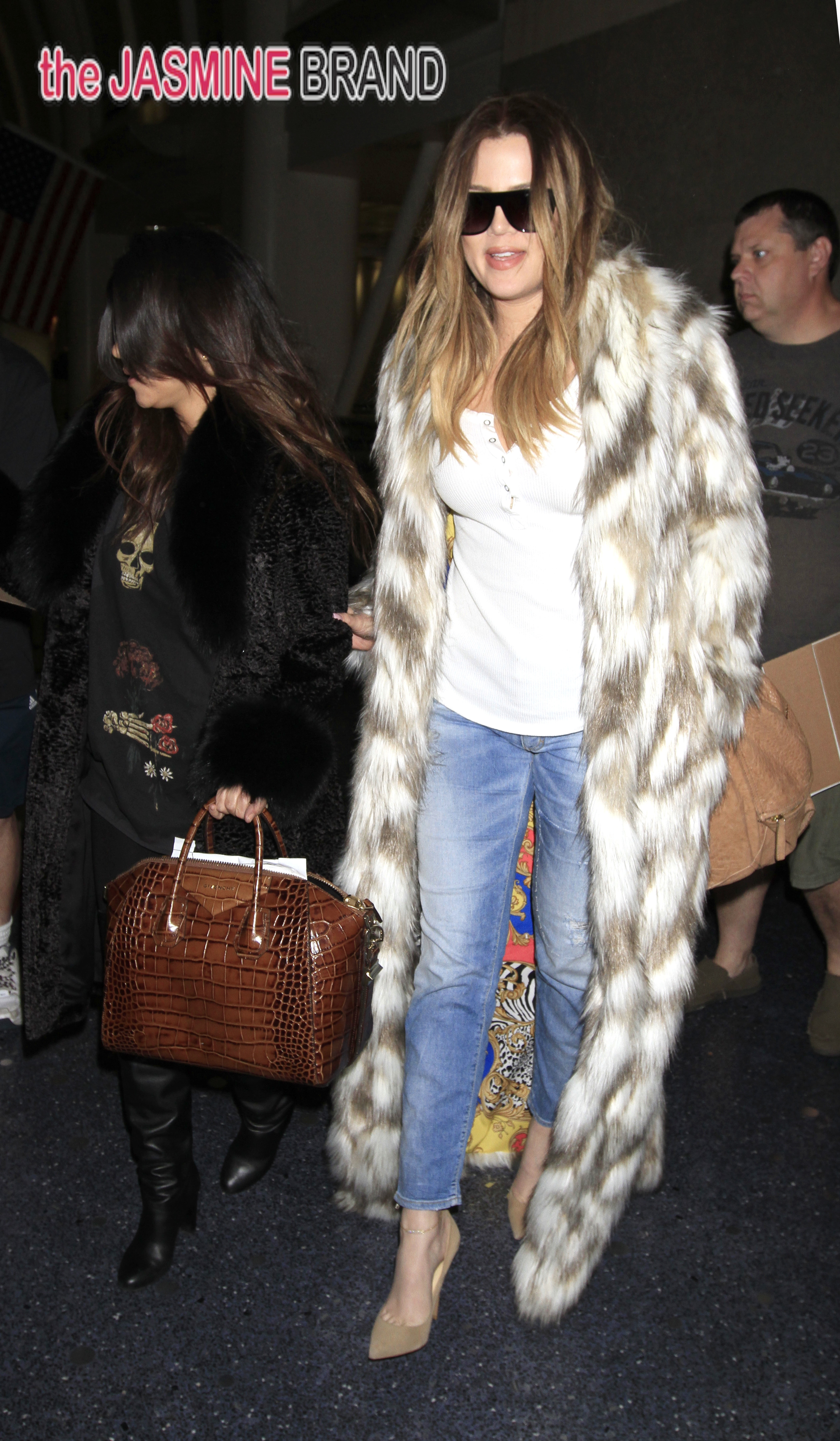 Khloe Kardashian wears a fur that says 'FXCK YO FUR' as she shows her support for banning for.  Kourtney Kardashian was also seen with her sister at LAX.