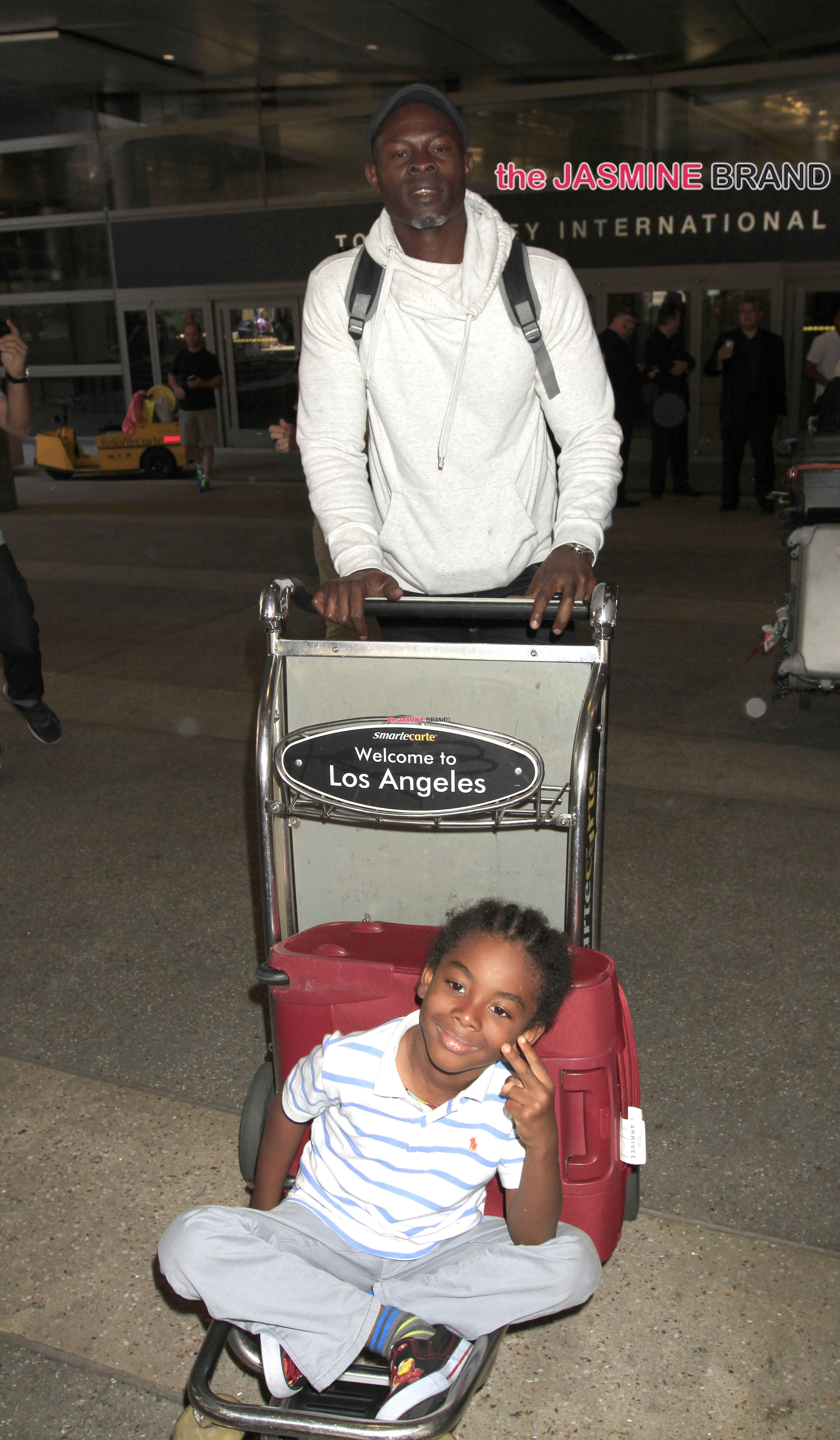 Djimon Hounsou pushes his son on a cart at LAX in Los Angeles
