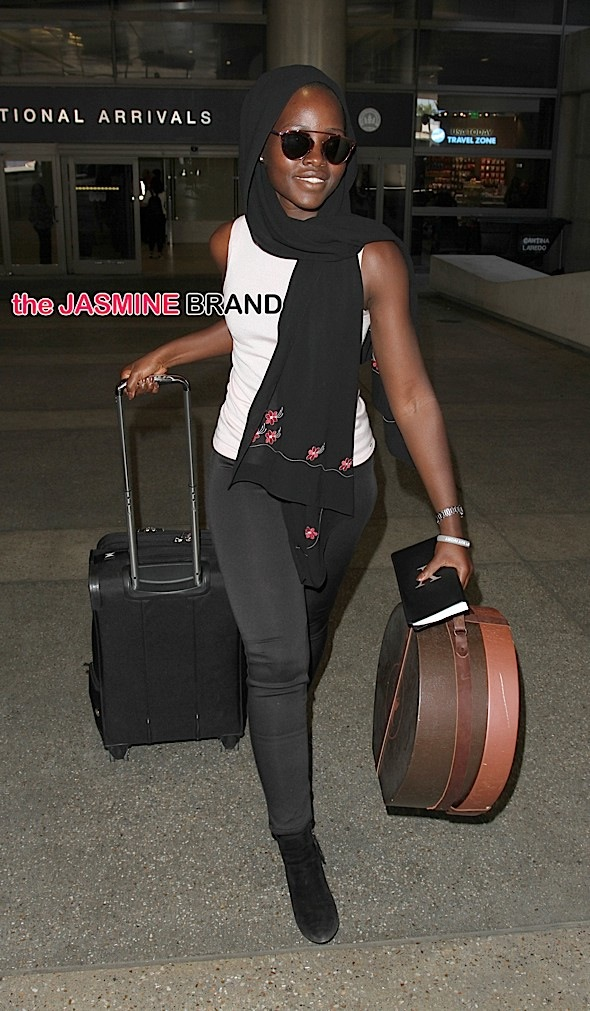 Oscar winning actress, Lupita Nyong'o arrives in Los Angeles carrying a hat in a carrier & a scarf around her head.