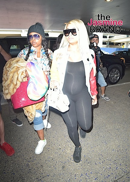 Blac Chyna and her growing baby bump arrive at LAX, swarmed by photogs.
